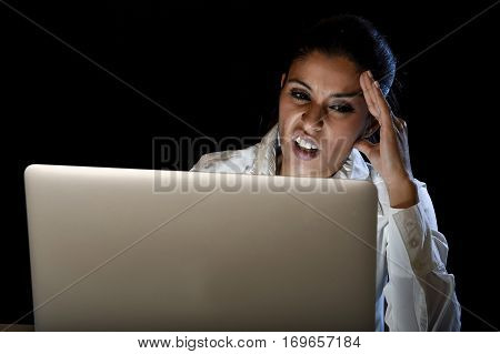 young business woman or student girl working in darkness on laptop computer late at night looking stressed bored and tired in long hours of work concept isolated on black background