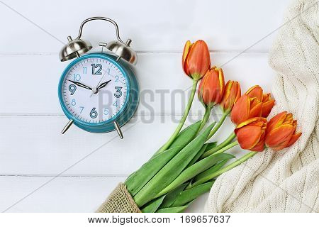 Alarm clock with a beautiful bouquet of tulips and a cozy blanket shot from above in a flatlay style over a wood table top. Daylight savings time concept.