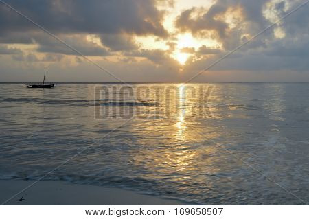 Dhow on the ocean at sunrise on Bamburi beach in Kenya