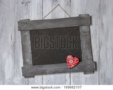 The old board with a red wooden heart hanging on a painted wall