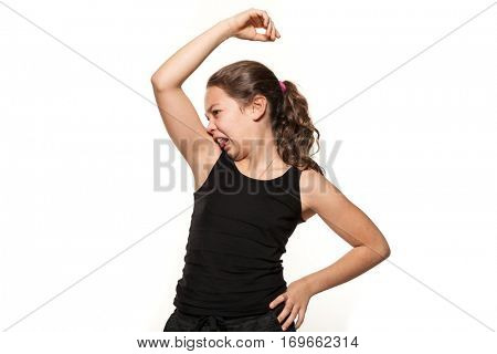 Girl smelling her armpit, isolated on white background