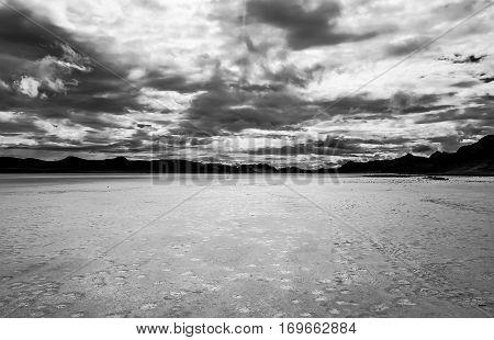 Black and white storm clouds over desert hardpan landscape