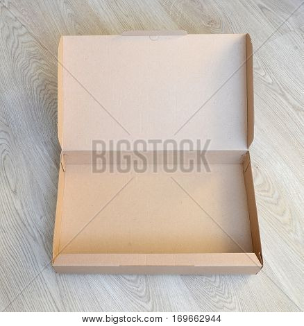 Empty cardboard box on a wooden floor.