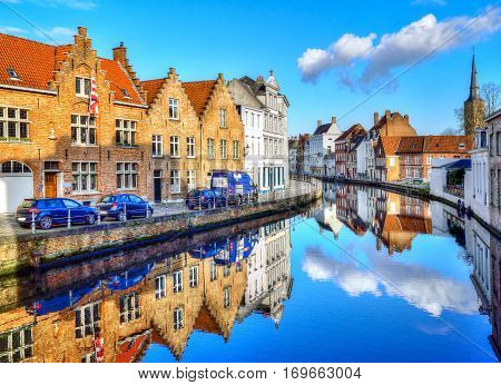 Traditional architecture along the canal reflected in water, in Brugge city Belgium