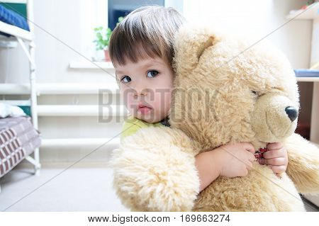 little girl hugging teddy bear indoor in her room devotion concept big bear toy