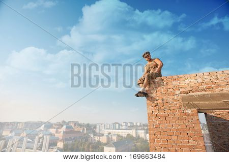 Muscular builder with bare torso in work wear sitting on brick wall on high. Man looking at camera and smiling. Extreme in hot summer day. Blue sky and cityscape on background.
