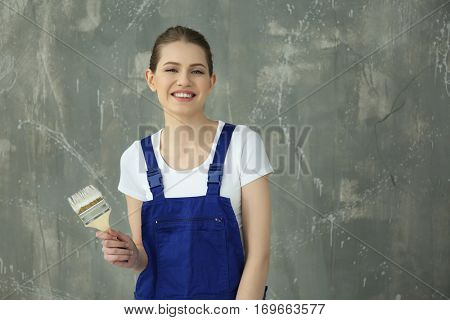 Young female decorator near grunge wall