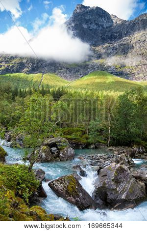 Norwegian landscape with milky blue glacier river near Trollstigen