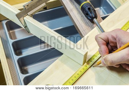 Assembling the kitchen drawer with a tray for the spoons and forks