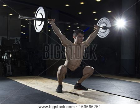 Muscular man doing the crossfit exercise in the gym.