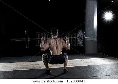 Muscular sportsman doing the  squat exercise in the gym at crossfit training.