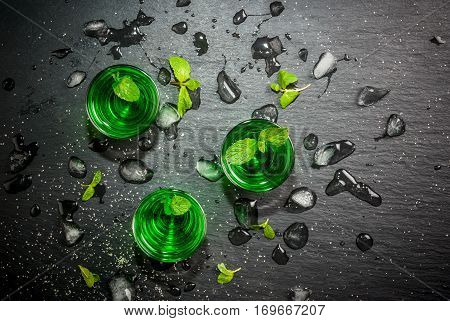 Sweet refreshing mint liqueur with ice and mint leaves on the slate tray to feed on gray concrete stone table top view copy space
