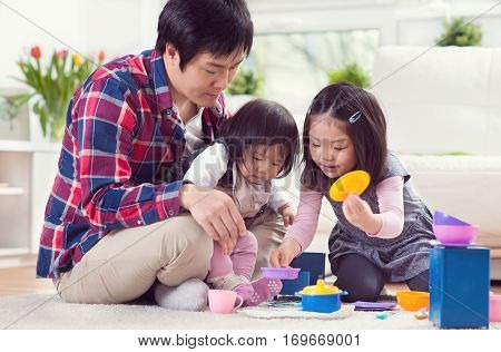 Young happy father playing with pretty daughters together and having fun at home