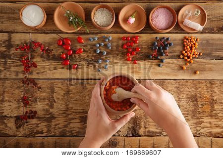 Woman making herbal cosmetic of natural ingredients on wooden background