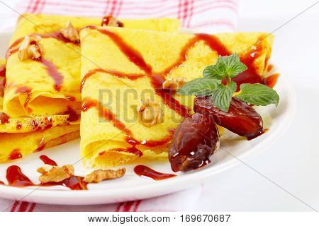pancakes with walnuts, dates and chocolate topping on white plate - close up