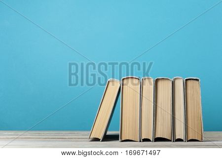 Stack of books on wooden table on colorful wall background.