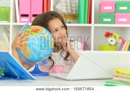 Portrait of a cute little girl doing lessons
