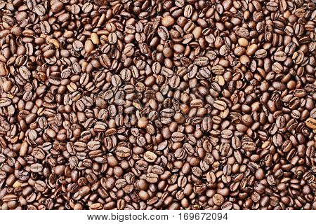 Overhead shot looking down on a flatlay image of a full frame of coffee beans background.
