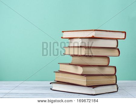 Composition with books on wooden table and colorful background.