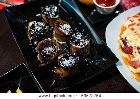 sweet rolls with topping for a delicious dessert on black plate