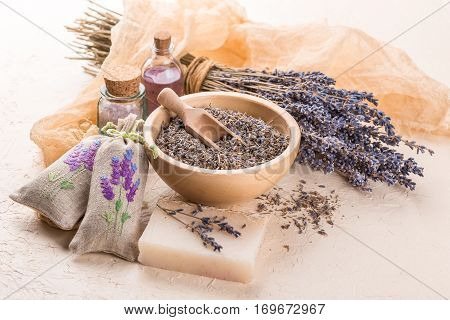 Wooden bowl with petals of lavender bottles of aromatic oil and salt sachets with embroidery homemade soap and dried lavender bouquet