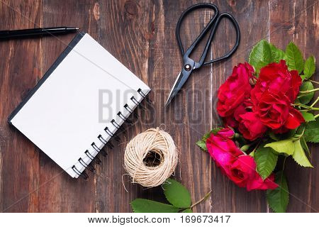 Beautiful Red Roses, Notepad, Scissors And Jute Rope On The Wooden Table