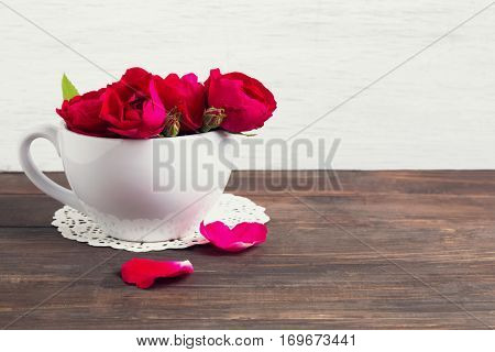 Bouquet Of Red Roses In A White Cup On The Wooden Table