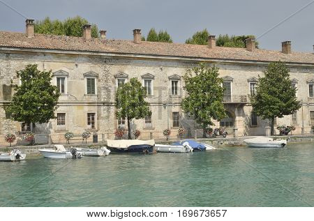 PESCHIERA DEL GARDA, ITALY - AUGUST 7, 2014: Boats parked at the river Mincio in front a building in Peschiera a village of Garda Lake and belong to the province of Verona in Veneto Italy.