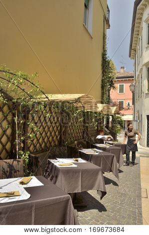 PESCHIERA DEL GARDA, ITALY - AUGUST 7, 2014: Row of restaurant tables in an alley of Peschiera a village of Garda Lake and belong to the province of Verona in Veneto Italy.