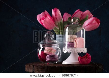 Colorful Tasty Macaroons In Glass Jars And Pink Tulips