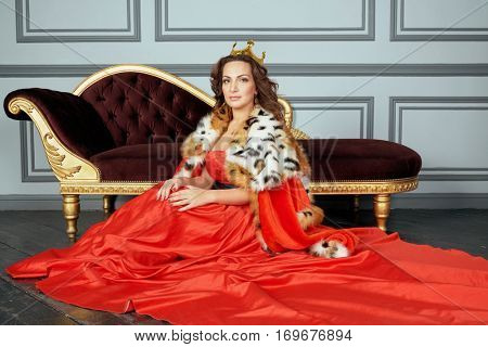 Woman in red dress, cloak and with crown on head sits on floor near couch in room.