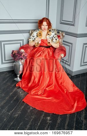 Red-haired woman in red dress and fur mantle sits in armchair in room.