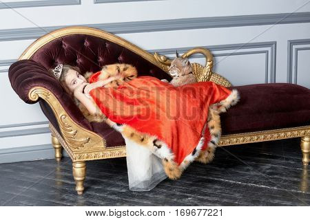 Girl with crown on head lies on couch covered by red cloak, lynx cub sits near.