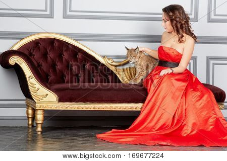 Woman in red dress sits on couch and plays with lynx cub.