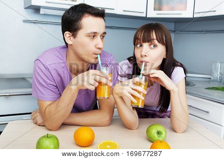 young cheerful couple drinking orange juice in the kitchen. healthy eating