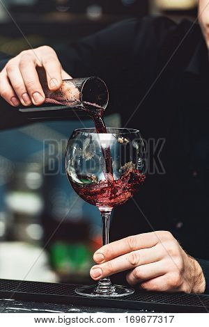 Barman pouring vine into glass in detail