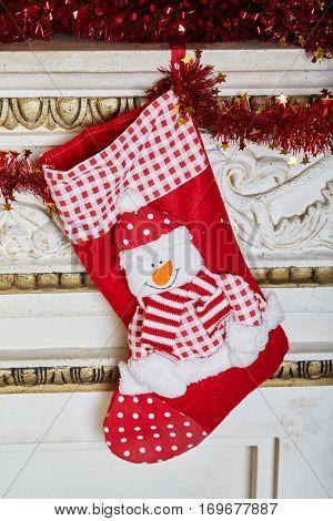 Gift boot hang on mantelshelf decorated to christmas holidays.