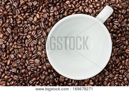 Overhead shot of an empty white cup over over a fresh background of whole coffee beans. Flat lay top view style.