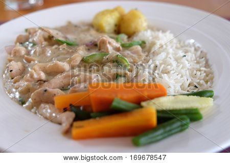 KOLKATA, INDIA - FEBRUARY 08: A meal of chicken stroganoff with white rice and vegetables in One Step Up restaurant in Kolkata, West Bengal, India on February 08, 2016 in Kolkata, India.