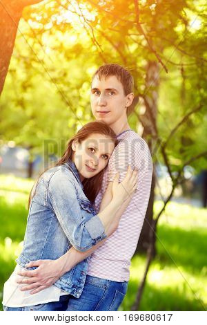 Young happy couple in love outdoors. loving man and woman on a walk in a summer park