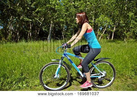 young woman riding a bike in a summer park. Active people outdoors. sport lifestyle