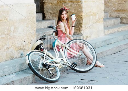 Young pretty blond-brown girl sitting on concrete stairs with a cup of coffee and looking toward, with vintage bicycle, in an old European city