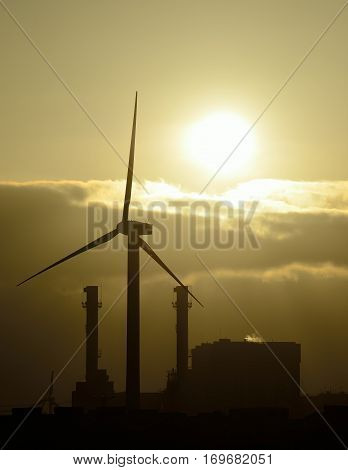 Power plant backlit and wind turbine at sunrise
