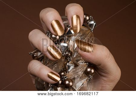 Female hand with shiny golden nails is holding brown jewel on brown background.