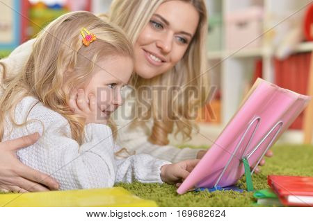 Portrait of a mother with little daughter reading book