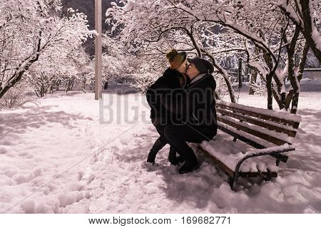 In winter a snowy night a woman sits on the lap of a man sitting on the bench and they kiss