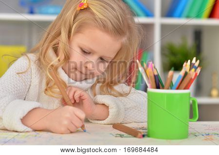 cute little girl drawing with colorful pencils