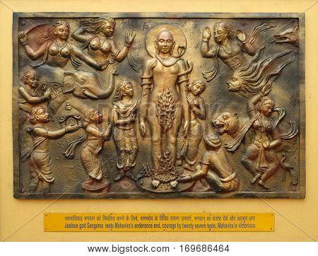 KOLKATA, INDIA - FEBRUARY 09, 2016: Jealous god Sangama tests Mahaviras enderance and, courage by twenty severe tests: Mahavira is victorius, Street bass relief on the wall of Jain Temple in Kolkata