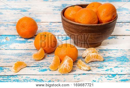 Bowl With Mandarins On Blue Wooden Table.