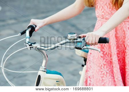 Close up hands of a young girl on old bicycle handlebar
